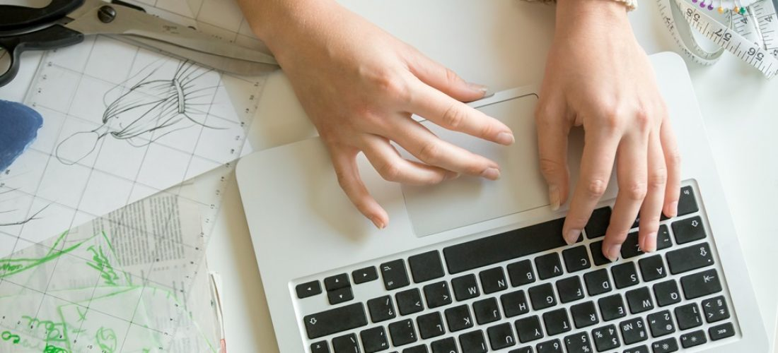 Hands working with a laptop, sewing accessories around. Concept photo, top view, horizontal, closeup, close-up